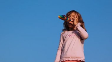Little girl blows in party blower on sky — Stock Video