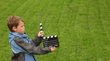 Boy says, claps clapperboard on grass — Stock Video