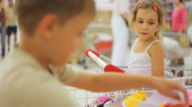 Boy and girl in supermarket with clothes — Vídeo Stock