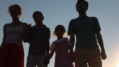 Familie van vier personen staat tegen hemel — Stockvideo