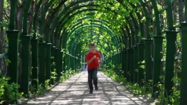 Boy runs through arched corridor braided green plants — Stock Video