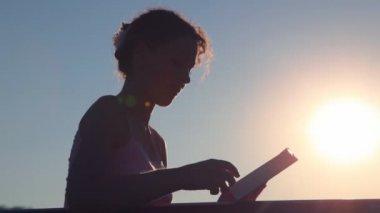 Mulher virando as páginas e ler o livro contra o céu do sol — Vídeo stock