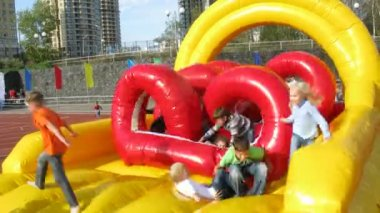 Children play on inflatable slide at stadium Yantar — Stock Video