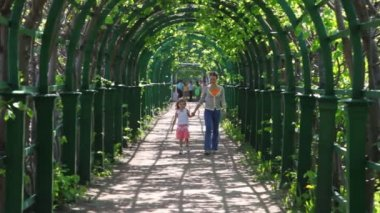 Mother and little daughter go through arched corridor braided plants — Stock Video