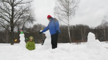 Kids and dad sculpt three snowmans, time lapse — Stock Video