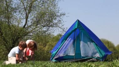 Boy and little girl pull cords of tent in woods — Stock Video