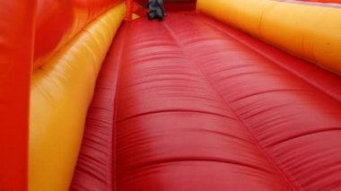 Boy drives off sitting and bouncing with inflatable rubber slides — Stock Video