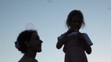 石鹸の泡とそれらをキャッチする母を吹く少女 — ストックビデオ