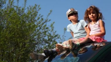 Boy in captain's cap and his sister sit on roof of car — Stockvideo