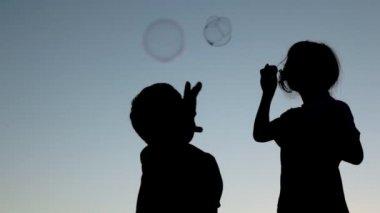 Mädchen bläst Seifenblasen und junge, die sie zu fassen — Stockvideo