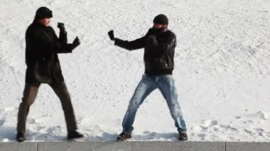 Men snowy winter playfully imitating boxing match — Stock Video