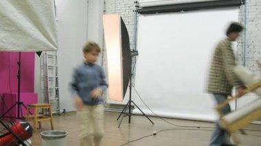 Photographer and his kid adjust equipment at photo studio — Stock Video
