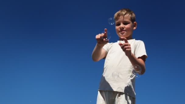 Boy catches and breaks his fingers flying on him soap bubbles — Vidéo