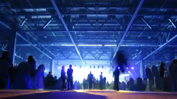 Siluetas de personas pasando frente a las luces brillantes — Vídeo de stock
