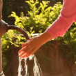 Woman washes her hands in stream of water from old rusty tap — Stock Video #28789149