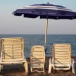 Chairs in three sizes are at seashore under umbrella — Stock Video