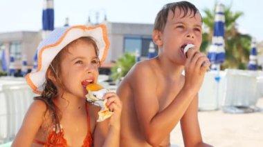 Menino e menina comem sorvete na praia — Vídeo stock