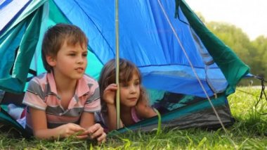 Boy with girl lay peeping out of tent, he something says at forest — Stock Video
