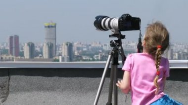Little girl on top of the roof play with digital camera — Stock Video