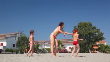Woman with male and female children play in hide and seek on beach — Stock Video