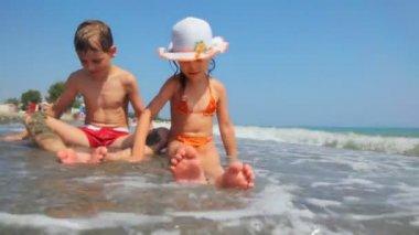 Fille et garçon assis au bord du rivage de la mer, jouer avec du sable — Vidéo
