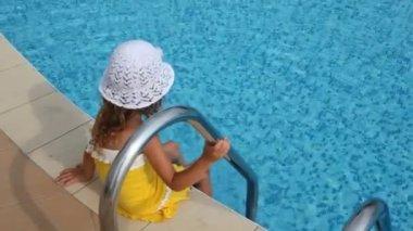 Garota senta-se na borda da piscina e apaga seus pés na água — Vídeo Stock
