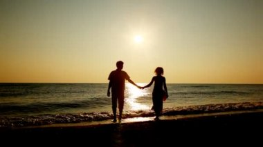 Mädchen und jungen gehen vom meer, silhouetten am sonnenuntergang, part2 händchen — Stockvideo