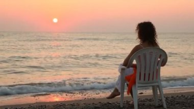 Woman sits on chair alone on beach faced to sea at sunset — Stock Video