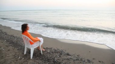 Woman sits on chair alone on beach and looks in distance pensive — Stock Video