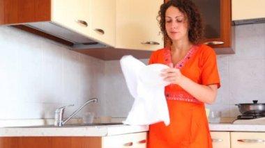 Flicka på köket torkar plattan och sätter det i skåp — Stockvideo