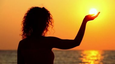 Young woman standing on beach, watching sunset — Stock Video