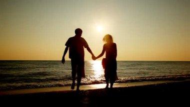 Jongen en meisje gaan op strand hand in hand voor zee, silhouetten op zonsondergang, part1 — Stockvideo