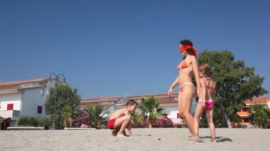 Blindfold woman with boy and gir play hide and seek on beach — Stock Video
