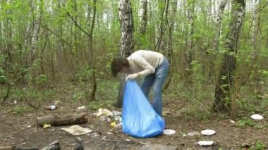 Man collects trash to garbage bag in forest — Stock Video