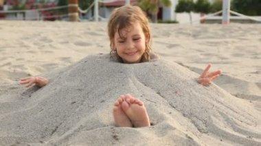 Sonrisas de niña pequeña emplazamiento llenan de arena en el cuello en la playa — Vídeo de Stock