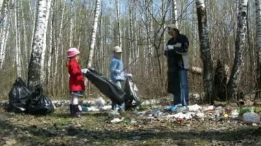 Children and their father collect trash to garbage bags in forest — Stock Video