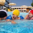 Stock Video: Boy and girls in swimming caps are talking in pool