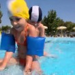 Stock Video: Girl and boy moving along border in pool one by one
