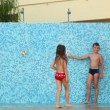 Stock Video: Little girl stands against wall with showers, but boy playfully turns on and off water