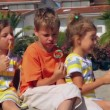 Tree kids eating lolly candy sitting on sand — Stock Video