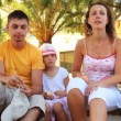 Family sits on bench among palm trees — Stock Video