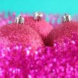 Three pink christmas tree balls rotate, surrounded by purple tinsel on blue background — Stok Video #28798071