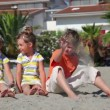 Two children sitting on sand and throw them against house — Stock Video #28798391