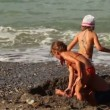 Three children dig pit in sand before sewater — Stock Video #28798433