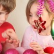 Girl and boy play with christmas-tree decoration — Stock Video #28798467