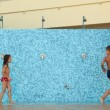 Girl with boy run along wall for showers playfully turned on and off water — Stock Video
