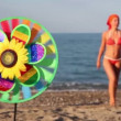 Toy with sunflower in center, that spins on the background of sea and woman — Stock Video