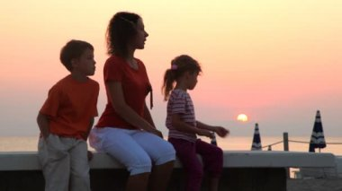 Mom and kids are sitting on bench and sun rises — Stock Video