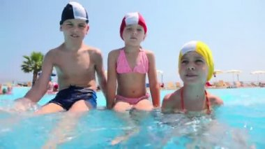 Boy and girls sitting in the pool, the boy splashes water — Stock Video