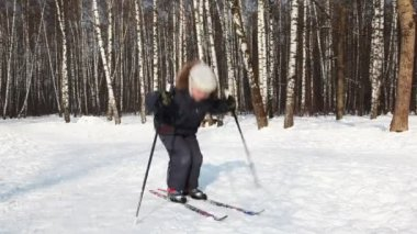 Young boy bounces on skis, pushing off sticks — Stock Video